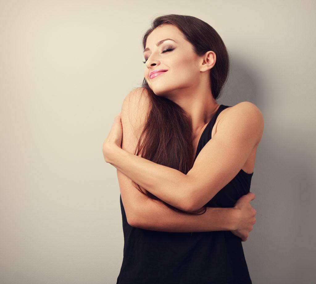Frau zeigt zufrieden ihre glatten Arme