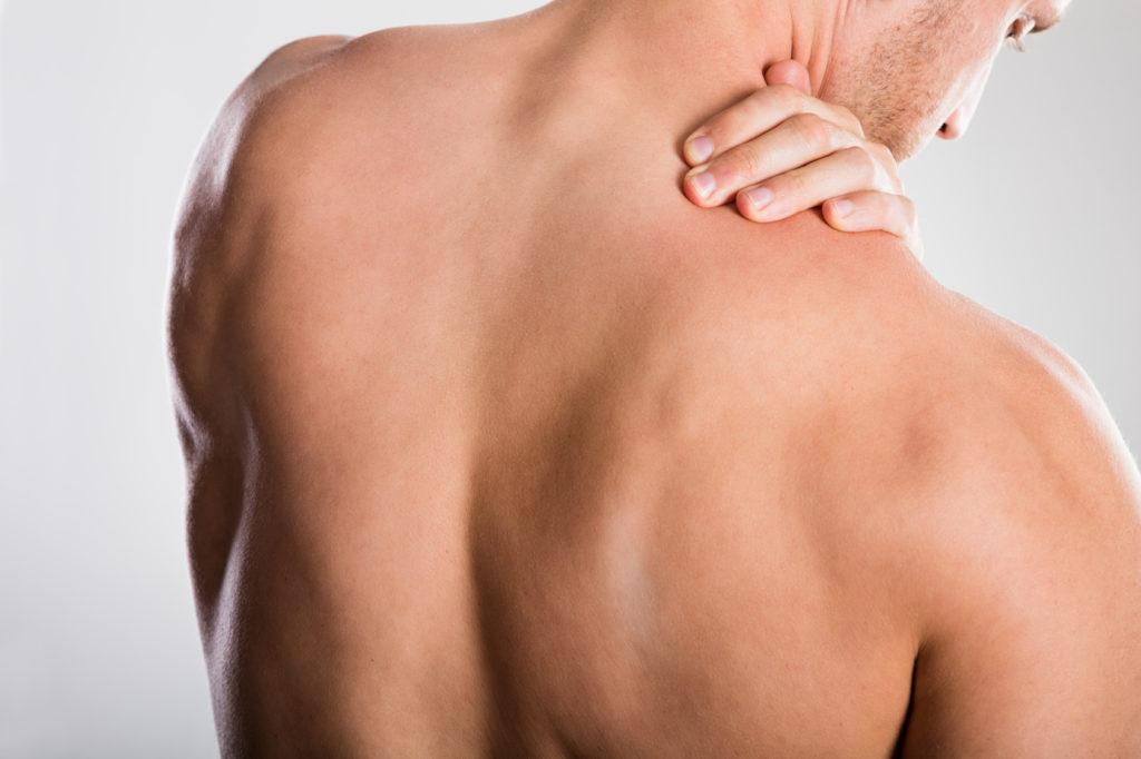 Mann greift sich an die Schulter